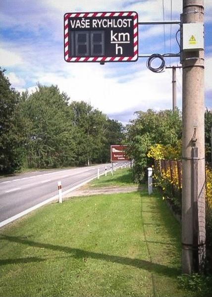 Měřič rychlosti osazený na sloupku a vyfocený v terénu v plném provozu