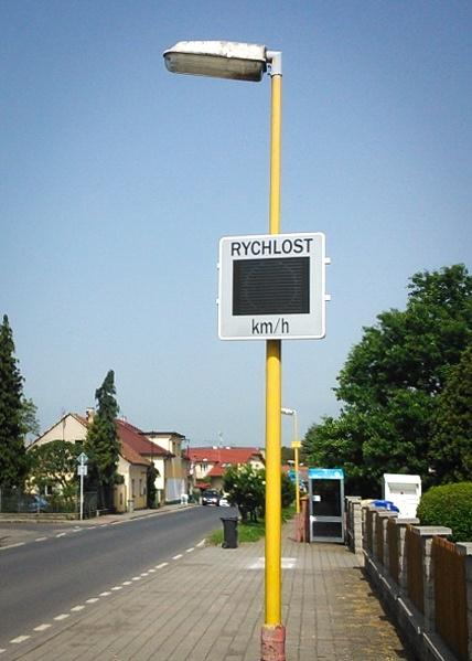 Měřič rychlosti osazený na sloupu veřejné lampy a vyfocený v terénu v plném provozu